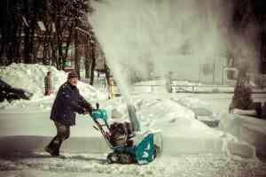 man using a snow blower
